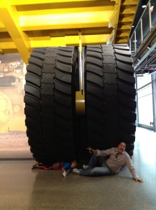 My husband and son under the wheel of the Caterpillar truck hired to bring my email to my office