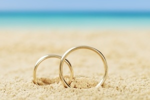 36192967 - photos of wedding rings on sand at beach